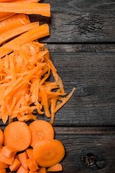 Pedaços de cenouras maduras. em fundo preto de madeira