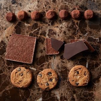 Pedaços de chocolate, balas de trufas e biscoitos em uma superfície de mármore escura