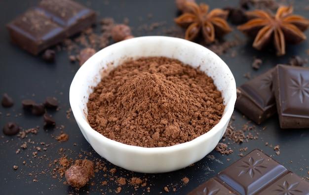 Pedaços de chocolate, cacau em pó e especiarias na mesa de ardósia escura, ingredientes para cozinhar