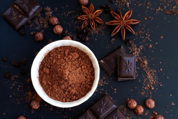 Pedaços de chocolate, cacau em pó e especiarias na mesa de ardósia escura, vista superior de ingredientes para cozinhar