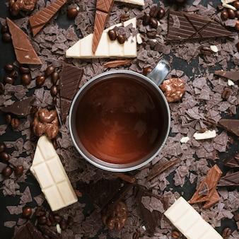 Pedaços de chocolate com grãos de café torrados; nozes e chocolate derretido no copo
