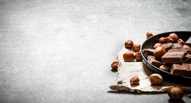 Pedaços de chocolate com nozes no prato velho. na mesa de madeira preta.