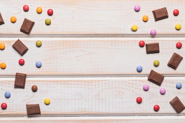 Pedaços de chocolate e gemas coloridas no cenário texturizado de madeira com espaço de cópia para escrever o texto