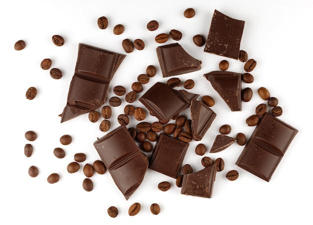 Pedaços de chocolate e grãos de café em uma superfície branca isolada