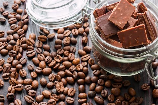 Pedaços de chocolate em uma jarra de vidro de grãos de café