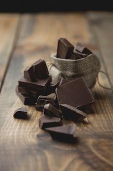 Pedaços de chocolate escuro em um saco de madeira