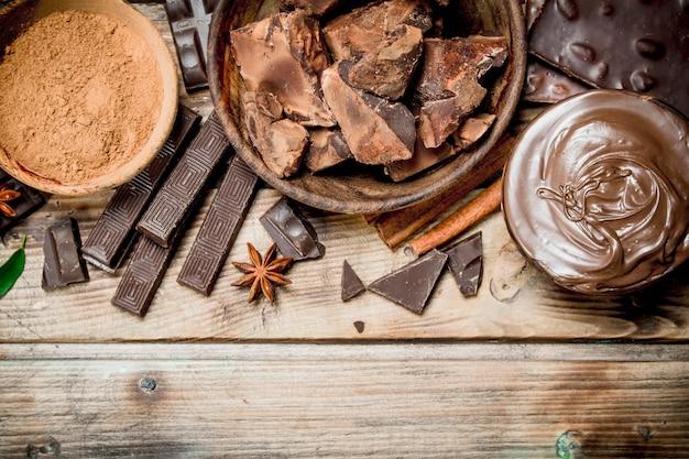 Pedaços de chocolate esmagado com pasta de chocolate e cacau em pó. sobre um fundo de madeira.