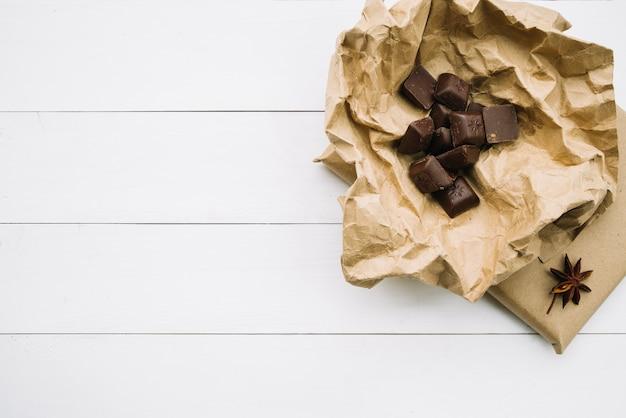 Pedaços de chocolate no papel amassado com anis estrelado em fundo branco de madeira