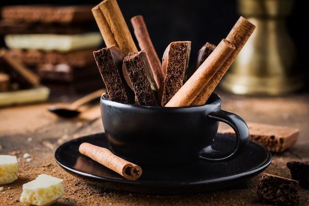 Pedaços de chocolate poroso e paus de canela em uma xícara de café preto