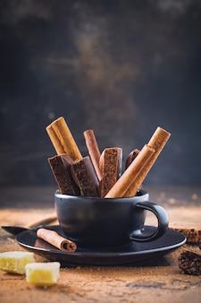 Pedaços de chocolate poroso e paus de canela na xícara de café preto na superfície velha escura. foco seletivo.