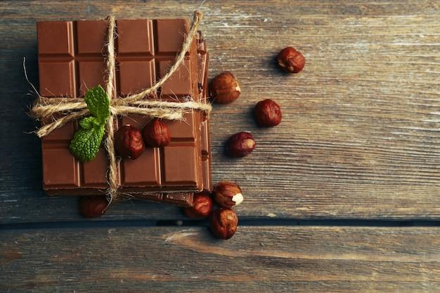 Pedaços de chocolate preto com nozes em fundo de madeira