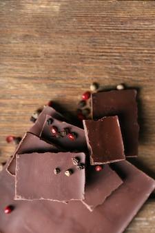 Pedaços de chocolate preto com pimenta na madeira