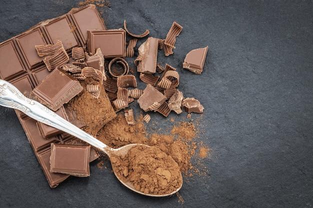 Pedaços de chocolate quebrados e cacau em pó no escuro.