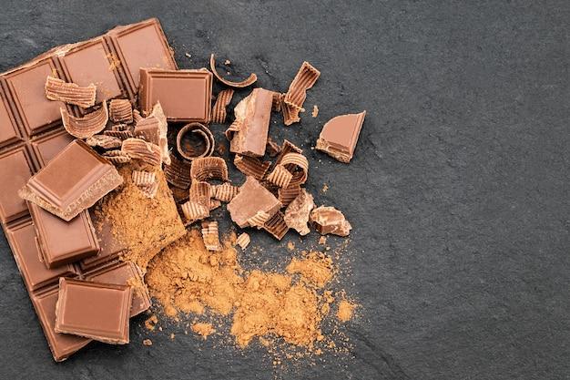 Pedaços de chocolate quebrados e raspas de chocolate em um fundo escuro.