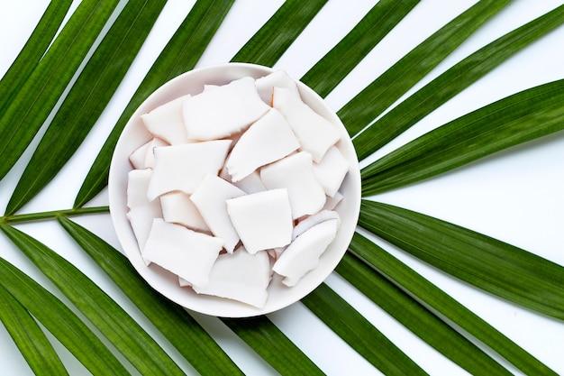Pedaços de coco no prato prato em folhas de palmeira tropical. vista do topo