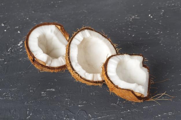 Pedaços de coco rachado em madeira escura