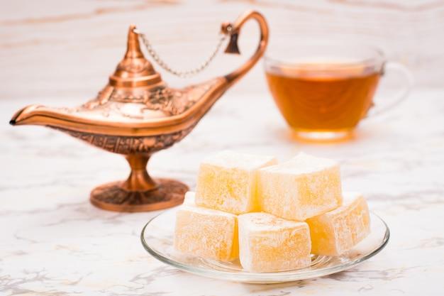 Pedaços de delícia turca em um prato e uma xícara de chá