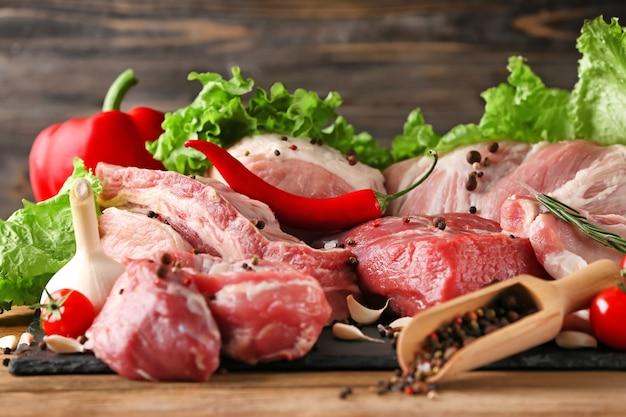 Pedaços de diferentes carnes frescas na mesa da cozinha