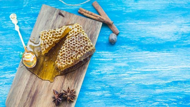 Pedaços de favo de mel e especiarias no plano de fundo texturizado azul
