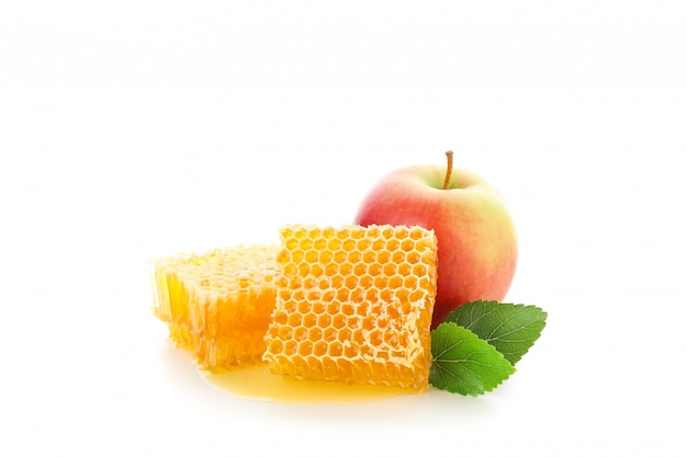 Pedaços de favo de mel e maçã isolado no branco