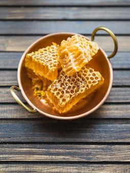 Pedaços de favo de mel no utensílio de cobre com alças na mesa de madeira