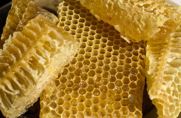 Pedaços de favo de mel. o mel flui dos favos de mel cortados frescos.