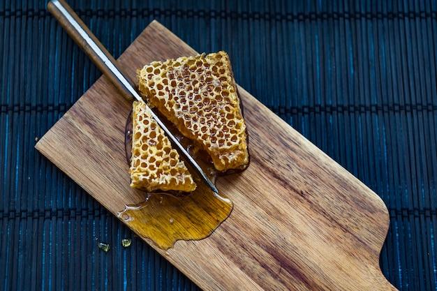 Pedaços de favo de mel sendo cortado com faca na tábua de madeira