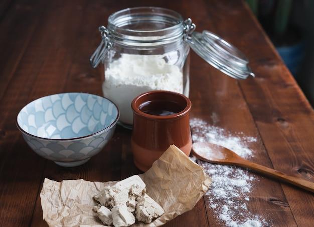 Pedaços de fermento em papel com recipientes e ingredientes em uma base de madeira para fazer fermento. conceito de padaria.