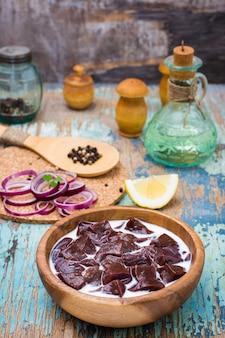 Pedaços de fígado bovino cru embebido em leite em uma tigela de madeira e ingredientes para cozinhar na mesa