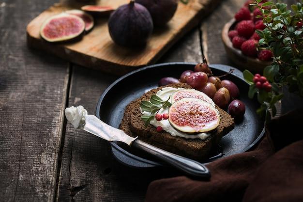 Pedaços de figos frescos com cream cheese no pão de centeio rústico.