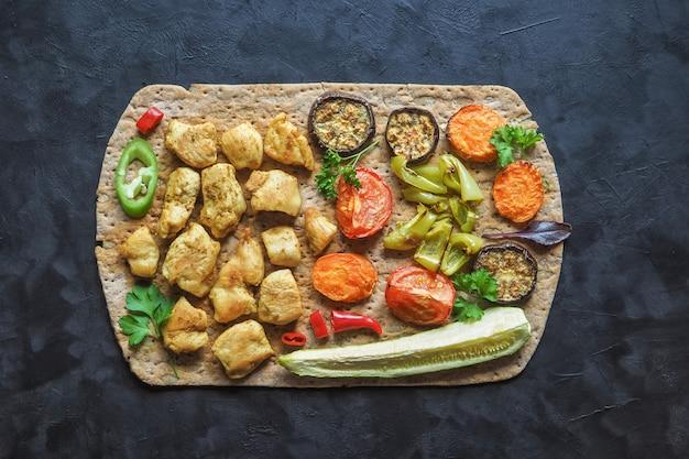 Pedaços de filé de frango frito no pão tortilla com legumes grelhados
