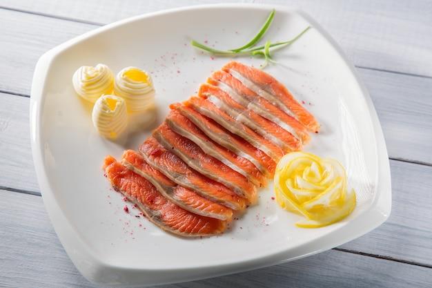 Pedaços de filé de salmão cru, servidos com especiarias, limão, manteiga e ervas na chapa branca e mesa de madeira