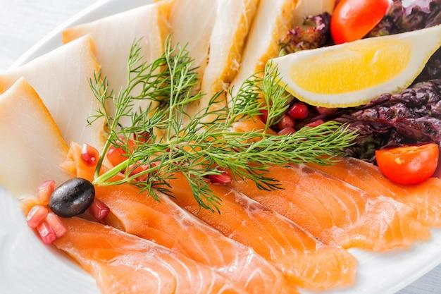 Pedaços de filé de salmão, pedaços de esturjão servidos com limão, azeitonas pretas, ervas, tomate cereja e sementes de romã na chapa branca