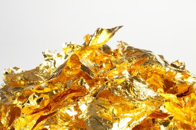 Pedaços de folha de ouro, um monte de elementos de decoração de papel de embrulho brilhante isolados no branco