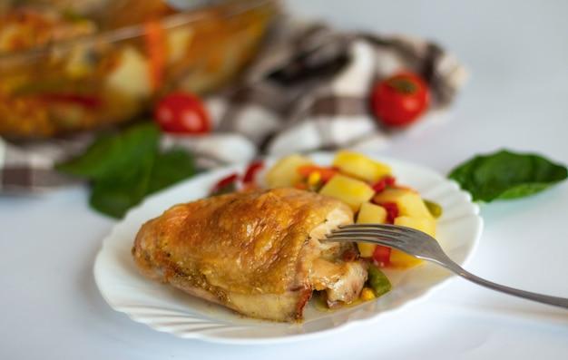 Pedaços de frango assado com legumes no prato
