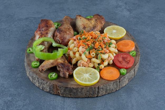 Pedaços de frango assado e macarrão no pedaço de madeira.