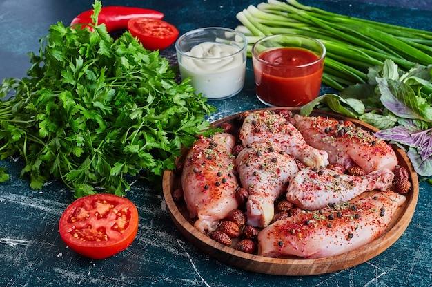 Pedaços de frango cru com ervas e especiarias.