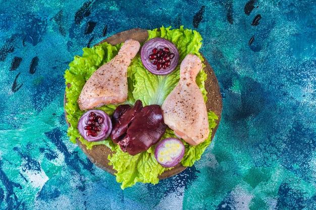 Pedaços de frango cru com legumes em uma placa