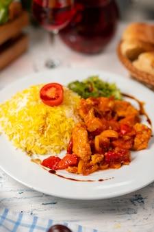 Pedaços de frango e cogumelo refogados em molho de tomate e servido com salada verde e enfeite de arroz