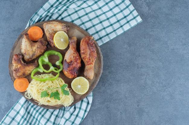 Pedaços de frango grelhado e espaguete no pedaço de madeira.