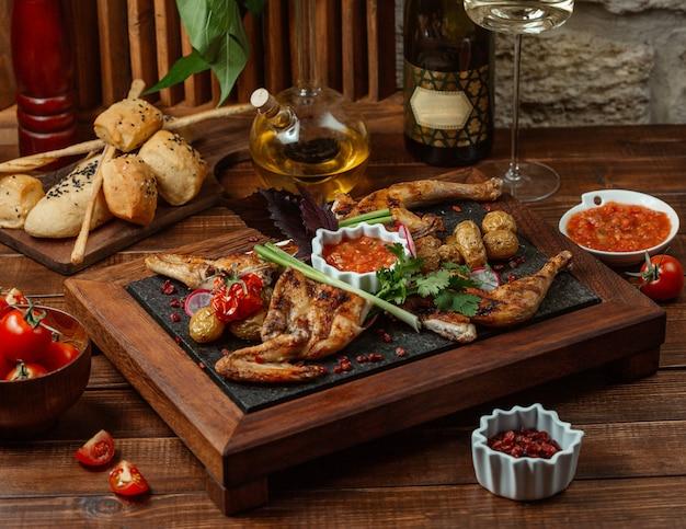 Pedaços de frango grelhado, guarnecidos com legumes e ervas, servidos com salada de beringela