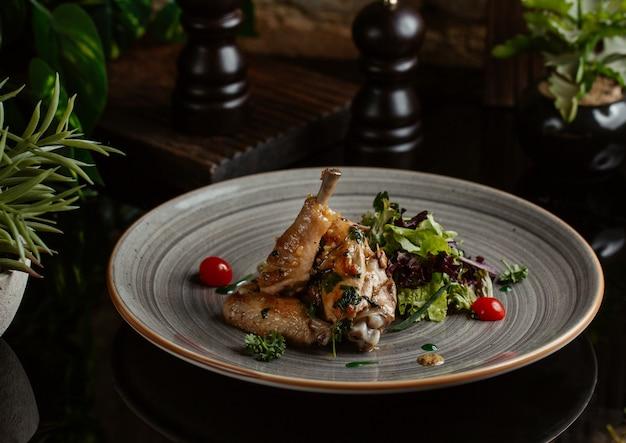 Pedaços de frango salteados em prato de cerâmica azul com salada