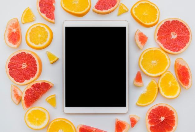 Pedaços de frutas cítricas em torno de tablet digital