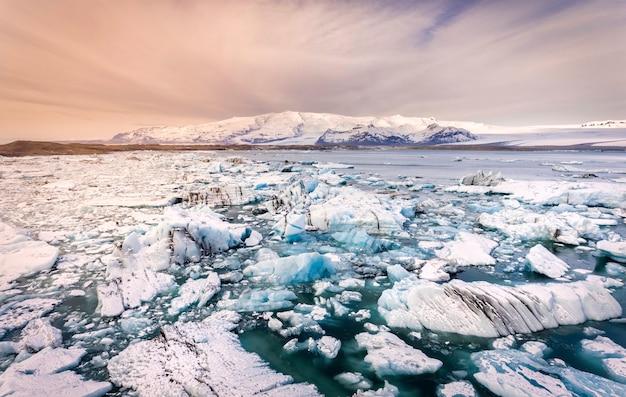 Pedaços de gelo espalhados por uma lagoa glaciar na islândia com montanhas cobertas de neve