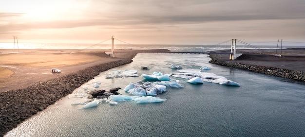 Pedaços de gelo espalhados por uma lagoa glaciar na islândia e uma ponte cruzando a imagem