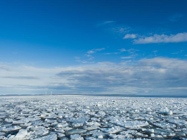 Pedaços de gelo no lago congelado sob o céu brilhante no inverno
