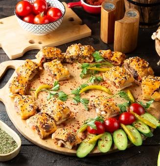 Pedaços de kebab beyti servidos na tábua de madeira com pepino e tomate