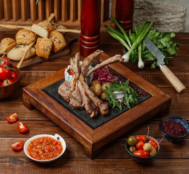 Pedaços de kebab de costelas de cordeiro servidos com batatas, ervas e salada de rabanete