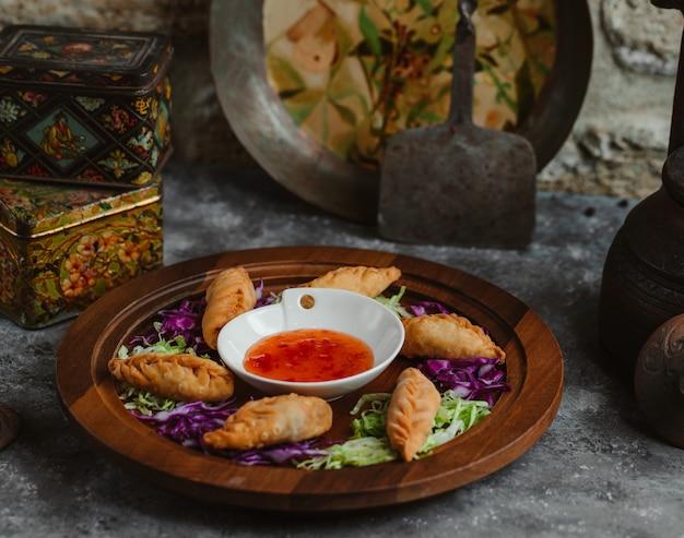 Pedaços de khingal assados servidos com molho de pimenta quente.