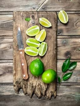 Pedaços de limão fresco em uma placa de corte com uma faca. em fundo de madeira